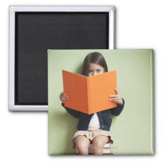 本の積み重ねに坐っている混血の女の子 マグネット