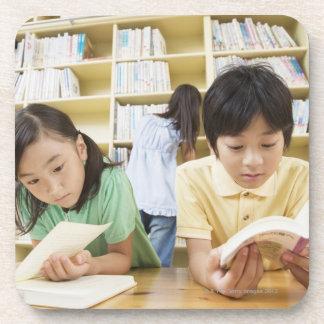 本を読んでいる小学校学生 コースター