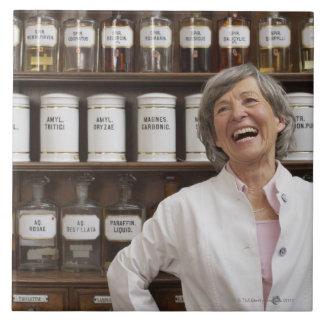 棚の前に立っている笑う薬剤師 タイル