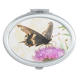 楕円形の鏡を引いている黒いアゲハチョウの蝶