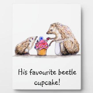 気色悪く薄気味悪いカップケーキを持つベビーのハリネズミ フォトプラーク
