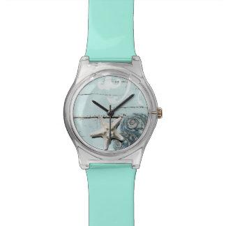 沿岸納屋の木製の水の青いヒトデの貝殻 腕時計