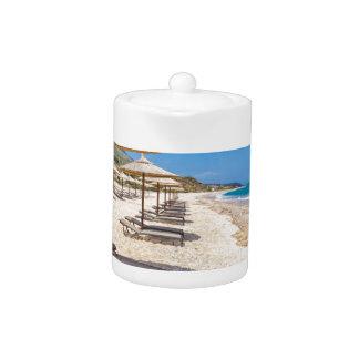 海が付いている砂浜の列のビーチパラソル