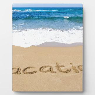 海で砂のビーチで書かれる単語の休暇 フォトプラーク
