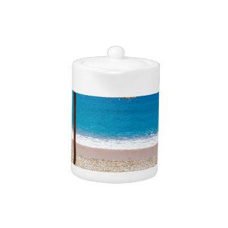海のビーチのloungersが付いているリードビーチパラソル