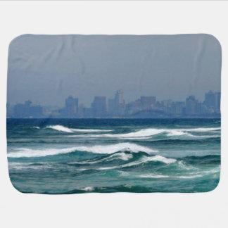 海の波の後ろの都市スカイライン ベビー ブランケット