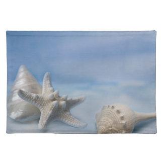 海は星の魚の手塗りの青い水彩画を殻から取り出します ランチョンマット