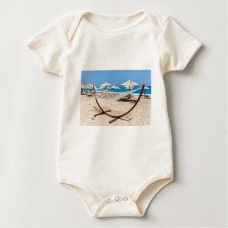 海岸のビーチパラソルが付いているハンモック ベビーボディスーツ