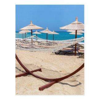 海岸のビーチパラソルが付いているハンモック ポストカード