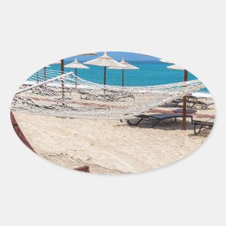 海岸のビーチパラソルが付いているハンモック 楕円形シール