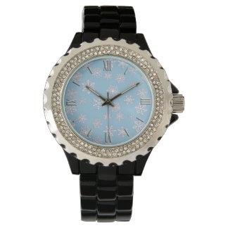淡青色の背景の白い3D雪片 腕時計