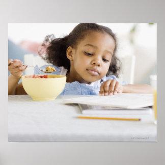 混血の女の子の読書および食べ物の朝食 ポスター
