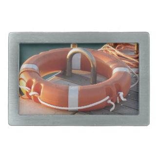 港の木桟橋のオレンジ救命ブイ 長方形ベルトバックル