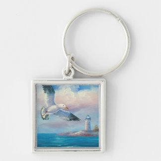 灯台の近くで飛んでいるカモメの絵画 キーホルダー