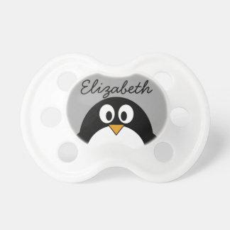 灰色の背景を持つかわいい漫画のペンギン おしゃぶり