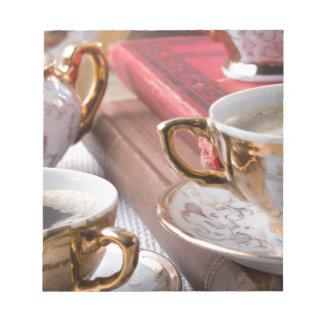 熱いエスプレッソが付いているヴィンテージのコーヒーカップおよびレトロ ノートパッド