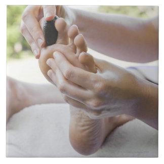 熱い石との足のマッサージを得ている女性 タイル