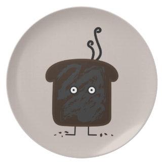 燃やされたトーストの煙は灰のパンを粉々にします プレート