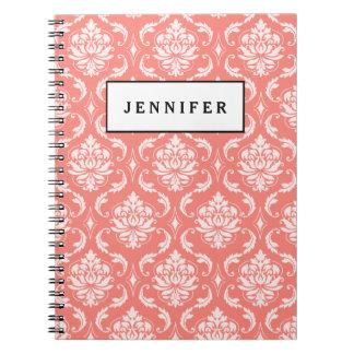 珊瑚のピンクの白くクラシックなダマスク織パターン ノートブック