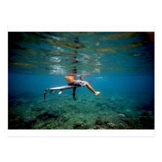 珊瑚礁上のサーフボードに坐っているサーファー ポストカード