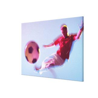 球を蹴るサッカーの選手のぼやけられた意見 キャンバスプリント