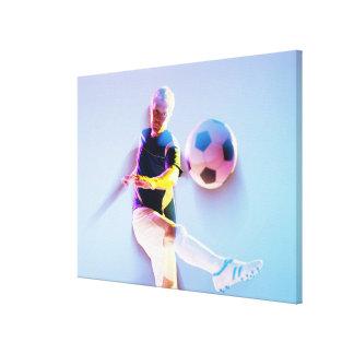 球2を蹴るサッカーの選手のぼやけられた意見 キャンバスプリント