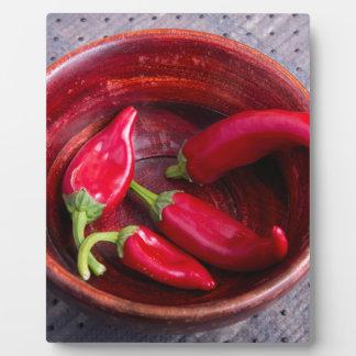 生地の背景の熱く赤いチリペッパー フォトプラーク