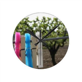 田園背景でつるす5つの色の洗濯ばさみ ラウンド壁時計
