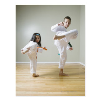 男の子および女の子(4-9)の練習のテコンドーの蹴り ポストカード