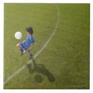 男の子(8-10)のフットボール選手の練習の技術、 タイル