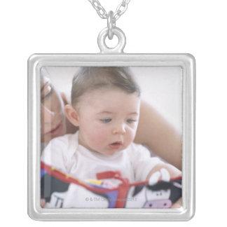 男の赤ちゃんに読んでいる母。 母の顔 シルバープレートネックレス