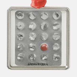 白で撮影されるプラスチック包装の最後の丸薬 メタルオーナメント