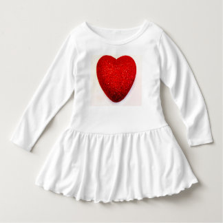 白人の大きい赤いハートが付いている幼児によって波立たせられる服 ドレス