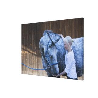 白馬を握る若い女の子のポートレート キャンバスプリント