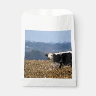 白黒牛は新たに耕された分野で牧草を食べます フェイバーバッグ