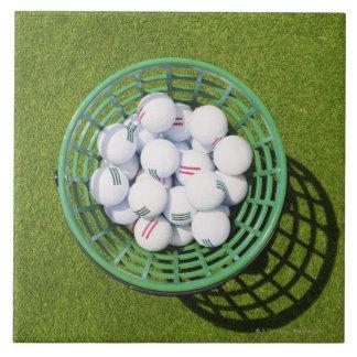 短い緑に坐るバスケットのゴルフ・ボール タイル