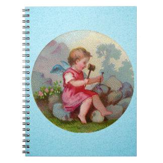石で切り分けているヴィンテージの天使の子供 ノートブック