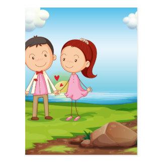 石の近くの川岸のカップル ポストカード