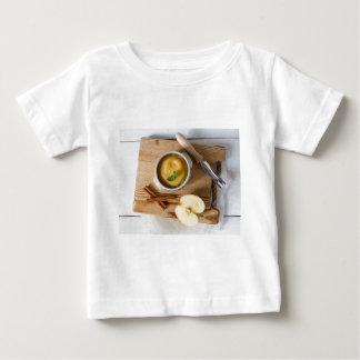 石器ボールのシナモンが付いているアップルソース ベビーTシャツ