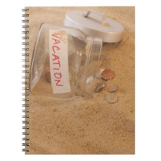砂でこぼれる硬貨が付いている瓶の閉めて下さい ノートブック