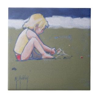 砂で遊ぶビーチの小さな女の子 タイル