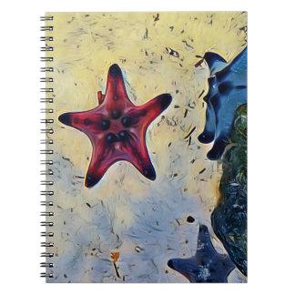 砂の芸術的で赤く青いヒトデ ノートブック