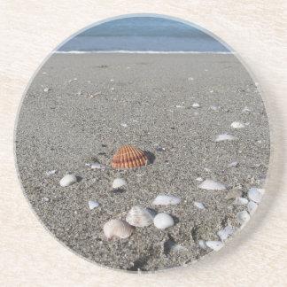 砂の貝殻。 夏のビーチの背景 コースター