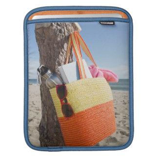 砂浜で木の幹でつるすバッグ iPadスリーブ