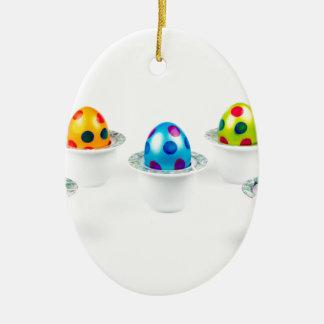 磁器のエッグカップに立つ色彩の鮮やかなイースターエッグ セラミックオーナメント