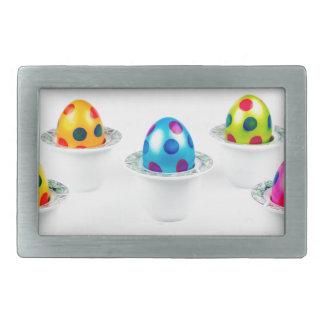 磁器のエッグカップに立つ色彩の鮮やかなイースターエッグ 長方形ベルトバックル