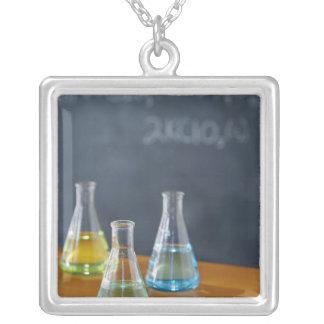科学の実験のために整理されるボトル シルバープレートネックレス