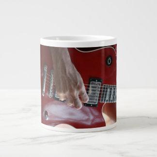 積み込みの近くで赤いエレキギターを演奏する手 ジャンボコーヒーマグカップ