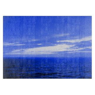 穏やかで青い海洋波の曇った日没の空の写真 カッティングボード