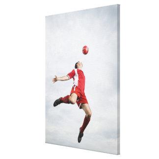 空中のサッカーの選手そしてサッカーボール キャンバスプリント